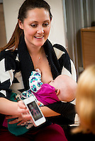 """A mother breastfeeds her baby while showing a picture on her mobile phone to another mum at a drop-in breastfeeding support centre.<br /> <br /> Image from the breastfeeding collection of the """"We Do It In Public"""" documentary photography picture library project: <br />  www.breastfeedinginpublic.co.uk<br /> <br /> Hampshire, England, UK<br /> 13/03/2013<br /> <br /> © Paul Carter / wdiip.co.uk"""