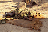 Kilamba, Tanzania; young child sleeping under a cloth on top of a sack on the ground.