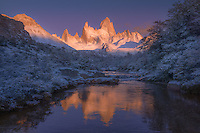 As the end of a prolonged rainstorm brought several inches of new snow to the landscape, the first light of day illuminates Cerro Fitz Roy, reflected in a small glacial stream below. A truly spectacular display of nature.