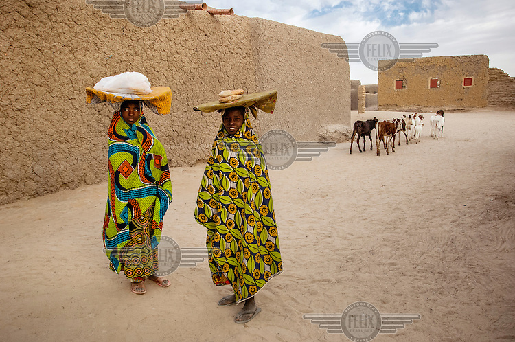 Children carry food on their heads in the town of Gao. /Felix Features