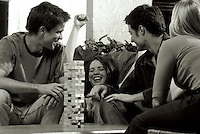 Smiling young couples playing a game of Jenga; laughing female gestures in triumph and satisfaction.