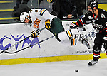 27 January 2012: University of Vermont Catamount forward Sebastian Stalberg, a Junior from Gothenburg, Sweden is tripped up by Northeastern University Husky defenseman Drew Ellement, a Junior from Winnipeg, Manitoba, at Gutterson Fieldhouse in Burlington, Vermont. The Catamounts fell to the Huskies 8-3 in the first game of their 2-game Hockey East weekend series. Mandatory Credit: Ed Wolfstein Photo