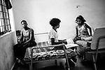 Anita Sodi (9) and Bharti Madkam (9) studies while Madvi Parmila (11) sits by the window at Sukma Football Academy girls' hostel.  Sukma, Chattisgarh, India. Arindam Mukherjee
