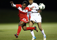BOYDS, MARYLAND - April 06, 2013:  Jasmyne Spencer (20) of The Washington Spirit is tripped by Morgan Stith (4) of the University of Virginia women's soccer team in a NWSL (National Women's Soccer League) pre season exhibition game at Maryland Soccerplex in Boyds, Maryland on April 06. Virginia won 6-3.
