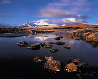 Snow-covered distant summits of the Blackmount (Clach Leathad) range seen across the River Ba, Rannoch Moor, Scottish Highland