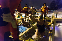 Moscow, Russia, 18/01/2016.<br /> A woman is helped from the water as Orthodox Christian believers celebrate Epiphany at a lake in southern Moscow. Priests blessed the waters and followers baptised themselves by total immersion in the freezing lake in temperatures of minus 11C.