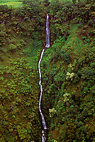 Close-up of a gorgeous white waterfall cascading through the mountain on the lush, remote Waipio Valley on the Hamakua coast of the Big Island of Hawaii.