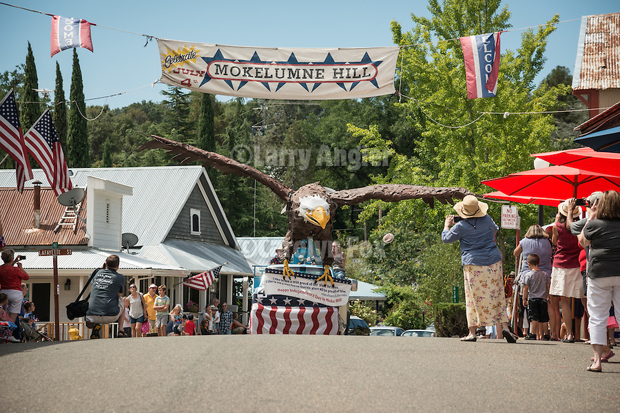 A giant eagle rides a boom truck of the Sandy Gulch Sign Company. Downtown main street during the Independence Day celebration Main Street, Mokelumne Hill, California