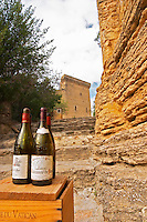 The ruin of the Pope's summer palace, only thing that is left of a splendid chateau.. Wine bottles on a wooden case in the foreground. Chateauneuf-du-Pape Châteauneuf, Vaucluse, Provence, France, Europe Chateauneuf-du-Pape Châteauneuf, Vaucluse, Provence, France, Europe