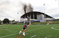 UVa lacrosse player Nick O'Reilly continues to practice with coach Marc Van Arsdale, behind, despite a large fire on the roof of the new UVa football practice facility Monday afternoon in Charlottesville, Va.