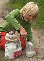 Kinder gießen Tierspur aus Gips, Junge füllt Gips in einen Messbecher