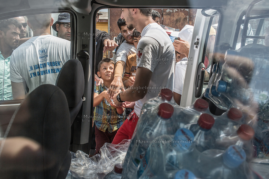 Distribuzione dell'acqua ai migranti da parte di Croce Rossa e volontari  UNHCR <br /> Distributing water to migrants by Red Cross  and UNHCR volunteers