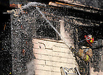Town of Manchester Fire Dept. Lt. Kevin Cooney, directs a stream of water on the outside wall from a second floor window of a home on at 9-11 Lilley Street in Manchester, Monday, November 17, 2008. The fire heavily damaged the second floor of the two family home, all the residents got  out safely but several small animals in cages were rescued by the fire department. Manchester was assisted by the 8th District and East Hartford fire Depts. on scene and the South Windsor fire dept for station coverage. (Jim Michaud/Journal Inquirer)