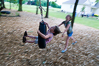 Young girls play on tire swing suspended from tree limb.