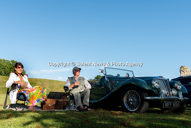 Pictured: Ann Marie Webley and Chris Richards enjoy the performance next to their 1954 MG TF 1500 during the Park & Picnic event at National Motor Museum, Beaulieu in the New Forest, Hants.<br /> <br /> The Park and Picnic event, allows motorists to park in bays designated for social distancing regulations and enjoy an evening of music and entertainment on the grounds of the National Motor Museum, Beaulieu.<br /> <br /> © Jordan Pettitt/Solent News & Photo Agency<br /> UK +44 (0) 2380 458800