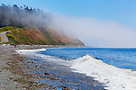 Fog drifts across a headland at Ebey's Landing National Historic Preserve, Whidbey Island, Washington.  Family plays on the beach.  Road winds up hill.