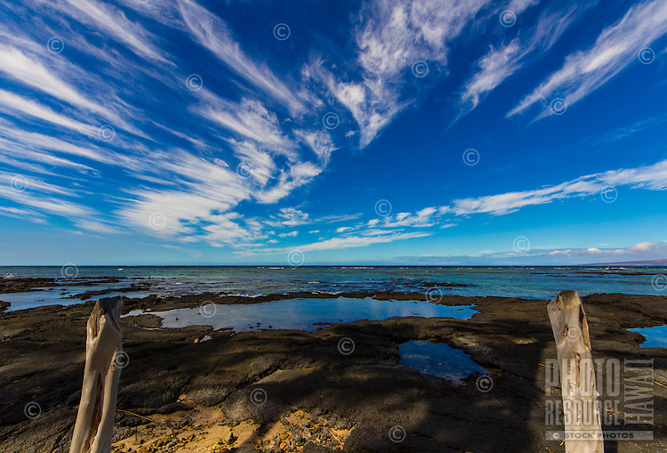 A quiet morning with streaking clouds that reflect off tide pools between two wooden posts, Puako, Big Island.