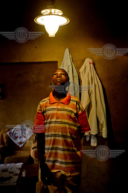 In Kayounga district, 60 kilometres from Kampala, a boy looks at a lamp fuelled by gas produced in a fermentation tank in the yard of the family house. The fermentation product, the result of a biogas process, supplies the house with gas, for light and for cooking.