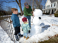 Jason Smith uses snow Saturday, Feb. 20, 2021, to form a mouth for a snowman that he built with his children, Abigail Smith, 2, and Logan Smith, 6, in front of their home on Lafayette Avenue in Fayetteville. The three took advantage of the warm morning to build the snowman complete with a carrot nose and charcoal eyes. Visit nwaonline.com/210221Daily/ for today's photo gallery. <br /> (NWA Democrat-Gazette/Andy Shupe)
