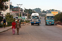 Myanmar, Burma, Kalaw.  Vehicular Traffic on a Main Street through Kalaw, Women Walking.