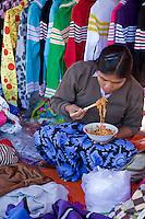 "Myanmar, Burma.  Clothing Vendor Eating Noodles with Chopsticks, ""Five-Day"" Market, Inle Lake, Shan State."