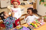 Education preschool 3 year olds pretend play and talking in kitchen family area two girls and a boy dressup and play food