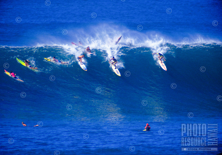 A row of surfers at the top of a large swell on the beautiful blue surf of north shore Oahu.