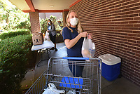 """WILLING PANTRY WORKERS<br />Kim Kay (left) and Whitney Chapman deliver grocery items to patraons on Tuesday Oct. 13 2020 at the St. Andrew's Episcopal Church food weekly food pantry in Rogers. Anyone in need of food is welcome to visit the pantry on Tuesdays from 9 to 11 a.m. at 820 W. Oak St. in Rogers. Patrons should stay in their vehicles and a volunteer will come to jot down some information and deliver the items. """"You can see the relief on the faces of the families, and that's nice,"""" Chapman said. About 15 church members and other volunteers operate the food pantry. Go to nwaonline.com/201014Daily/ to see more photos.<br />(NWA Democrat-Gazette/Flip Putthoff)"""