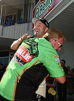 Sept. 23, 2012; Ennis, TX, USA: NHRA top fuel dragster driver Terry McMillen (in green) gives a bear hug to Bob Vandergriff Jr during the Fall Nationals at the Texas Motorplex. Mandatory Credit: Mark J. Rebilas-