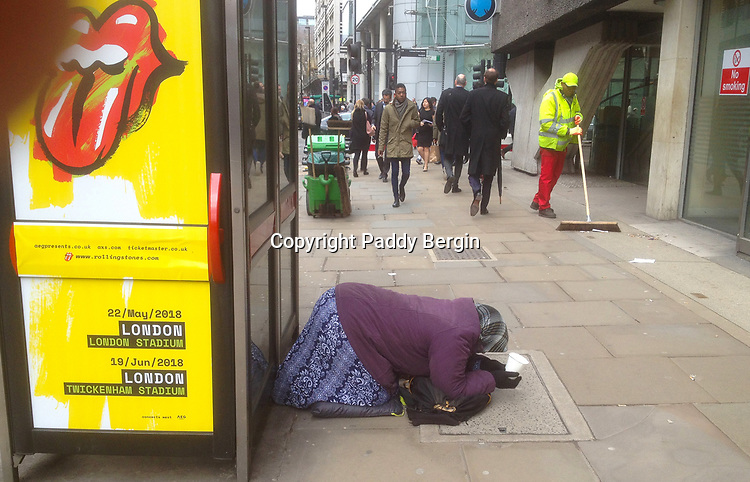 Woman kneeling in Moorgate in the City of London and holding a white plastic cup to collect donations in. Rolling Stones poster.<br /> <br /> A street sweeper and pedestrians in the background.<br /> <br /> Stock Photo by Paddy Bergin