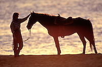 Woman petting her horse next to the waters of sunset beach, Oahu