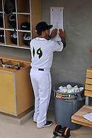 Manager Jose Leger (19) of the Columbia Fireflies posts the first roster in the dugout before the home opener against the Greenville Drive on Thursday, April 14, 2016, their first day at the new Spirit Communications Park in Columbia, South Carolina. The Mets affiliate moved to Columbia this year from Savannah. Columbia won, 4-1. (Tom Priddy/Four Seam Images)