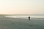 Ngwe Saung beach at dawn, local people stroll before going to work in the new hotel resorts. Burma Myanmar. 2011.