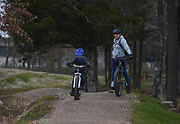 """Emily Howard of Bentonville (right) looks on as Theo Howard, 7, (left) rides, Monday, January 11, 2021 along the Mama Bear trail in Bentonville. """"This one is honestly really fun for the kids, and one of the only ones you can ride when it's really muddy and cold out there,"""" said the boy's mom, Emily Howard of Bentonville. Check out nwaonline.com/210112Daily/ for today's photo gallery. <br /> (NWA Democrat-Gazette/Charlie Kaijo)"""