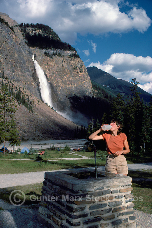 Yoho National Park, Canadian Rockies, BC, British Columbia, Canada - Hiker drinking Water in Campground at Takakkaw Falls and Yoho River, Summer (Model Released)