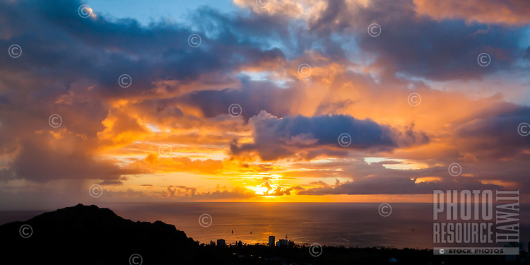 An aerial view of the rays of a fiery sunset beaming through clouds, with the peak of Diamond Head in silhouette at left, Honolulu, O'ahu.