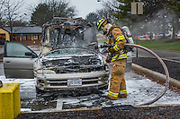 Westerville fire fighter checks the engine compartment of a car that burned in the Kroger parking lot on Schrock Rd. in Westerville