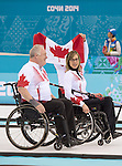 Sochi, RUSSIA - Mar 15 2014 - Sonja Gaudet, Jim Armstrong and Dennis Thiessen (holding flag) celebrate their gold medal win in the Gold Medal Wheechair Curling match at the 2014 Paralympic Winter Games in Sochi, Russia.  (Photo: Matthew Murnaghan/Canadian Paralympic Committee)