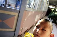 CHINA. Beijing. A young, mentally handicapped orphan in an orphanage outside of Beijing. 2007. There are currently millions of orphans in China living in orphanages spread throughout the country. As a result of China's one-child policy, many children are abandoned or given up if they suffer from any physical or mental handicap as the parents strive to have a child born 'normal' and well. This has led to may children being abandoned to live in state and privately-owned orphanages.