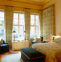 Matching green and cream floral fabric has been used for both the bed cover and the curtains in this bedroom