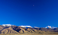Near-barren tendrils of desert, like fat giant fingers, rise to the snow covered peaks of Humboldt National Forest, Nevada.  The quarter moon stands watch.
