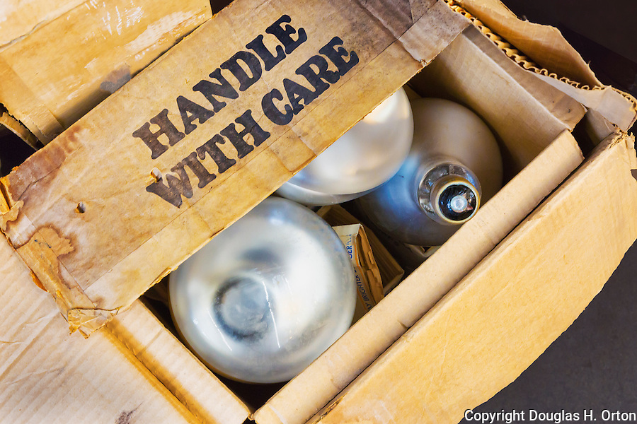 """Old cardboard box labled """"Handle With Care"""" containing florescent flood lights."""