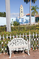 Cuba, Trinidad.  Wrought-iron Chair in the Plaza de Armas.  Bell Tower of the Church and Convent of San Francisco in the rear.