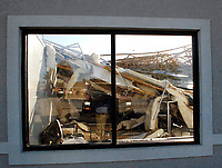 Marc Hayot/Herald-Leader<br /> A view through a window at the Eastgate Shopping Center along U.S. Highway 412 in Siloam Springs shows the roof is missing and heavy damage inside the building after severe storms during the early hours of Monday morning.
