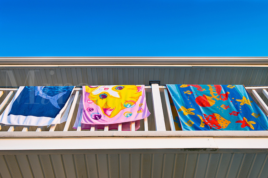 Beach towels dry on hotel balcony.