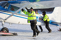 Volunteer Iditarod Air Force Director of Maintenance, Loren Gerrety, and pilots Greg Fishcer and Daniel Hayden push Fischer's plane to a holding area at the Willow, Alaska airport during the Food Flyout on Saturday, February 20, 2016.  Iditarod 2016