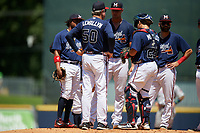 Mississippi Braves pitching coach Dennis Lewallyn (50) talks with starting pitcher Kyle Muller (8) as third baseman Luis Valenzuela (left), catcher Jonathan Morales (28), and second baseman Alejandro Salazar (right) listen in during a Southern League game against the Jacksonville Jumbo Shrimp on May 5, 2019 at Trustmark Park in Pearl, Mississippi.  Mississippi defeated Jacksonville 1-0 in ten innings.  (Mike Janes/Four Seam Images)