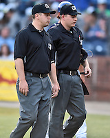 First base umpire Matt Carlyon and home plate umpire Ryan Powers go to discuss the situation with both managers between innings in a game against the Hagerstown Suns at McCormick Field on April 28, 2016 in Asheville, North Carolina. The Tourists were leading the Suns 6-5 when the game was delayed in the top of the 6th inning due to darkness. (Tony Farlow/Four Seam Images)