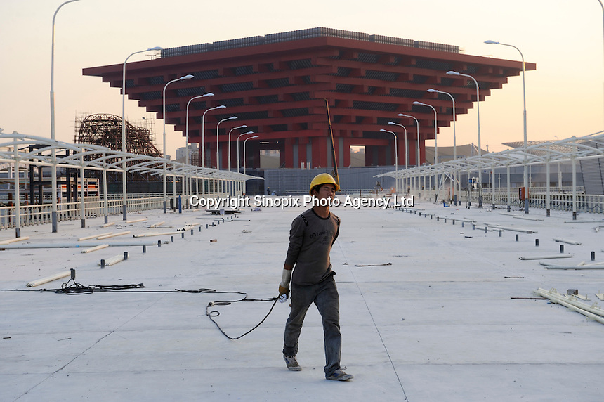 """Chinese workers at the construction site of China Pavilion of the World Expo 2010 in Shanghai, China. The China Pavilion is designed with the concept of """"Oriental Crown."""" The traditional Chinese wooden structure element, Dougong brackets, is introduced. Its main colour is """"Gugong (Forbidden City) Red"""" which represents the taste and spirit of Chinese culture. The permanent facilities including the World Expo Axis, Chinese Pavilion, Theme Pavilion, Performance Center and Expo Center of the World Expo 2010, will be completed by the end of this year..15 Oct 2009"""