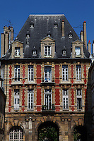 Paris Right Bank: The ancient building at the entrance from rue de Bretagne of place des Vosges (XVII century), with its three arcs, its red bricks, and its particular roof in slate. This is the Pavillon du Roi (the Pavillon of the King), on the background of a blue sky.<br /> <br /> You can download this file for (E&PU) only, but you can find in the collection the same one available instead for (Adv).